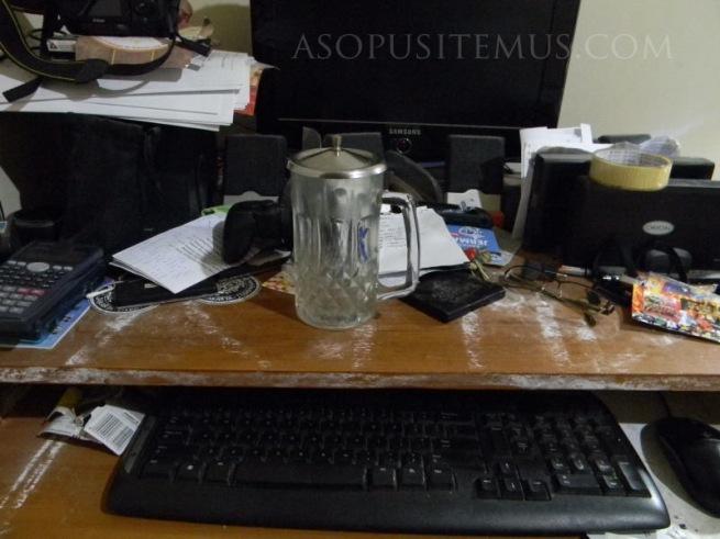 komputer dan gelas minuman di meja